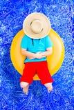 Het gelukkige jonge jongen ontspannen op een buis in de pool stock afbeelding