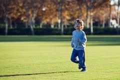 Het gelukkige jonge jongen spelen met rode bal op groen gras Royalty-vrije Stock Afbeelding