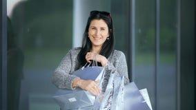 Het gelukkige jonge maniervrouw stellen met het winkelen doet dichtbij het wandelgalerijvenster in zakken stock video
