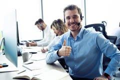 Het gelukkige jonge mannelijke klantenondersteuning uitvoerende werken in bureau stock afbeelding