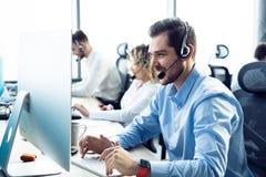 Het gelukkige jonge mannelijke klantenondersteuning uitvoerende werken in bureau royalty-vrije stock afbeeldingen