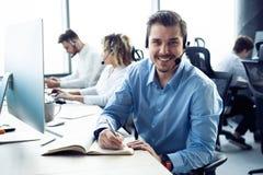 Het gelukkige jonge mannelijke klantenondersteuning uitvoerende werken in bureau stock afbeeldingen