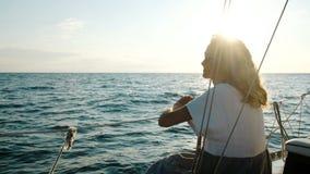 Het gelukkige jonge meisje in een kleding zit op het dek en het slingeren op de golven in het overzees stock footage
