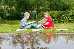 Het gelukkige Jonge meisje en jongens Schrijven Binnen het glimlachen Stock Afbeelding