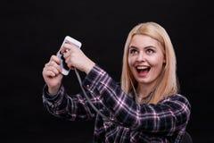 Het gelukkige jonge meisje luistert aan een smartphone gebruikend een stethoscoop en lacht Zwarte achtergrond royalty-vrije stock foto's