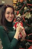 Het gelukkige jonge meisje met hond kleedde zich in Santa Claus-kleren op Kerstboomachtergrond royalty-vrije stock foto