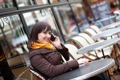 Het gelukkige jonge meisje takling op celtelefoon stock foto