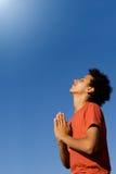 Het gelukkige jonge mens bidden stock foto