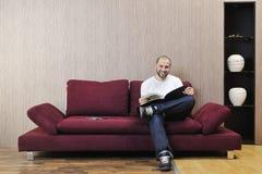 Het gelukkige jonge mens realxing in moderne woonkamer stock fotografie