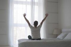 Het gelukkige jonge mens uitrekken zich in bed na ontwaken, achtermening royalty-vrije stock afbeelding