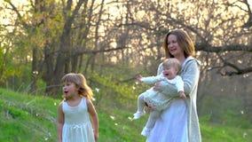 Het gelukkige jonge moeder spelen met haar dochters in het park stock footage