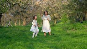 Het gelukkige jonge moeder spelen met haar dochters in het park stock videobeelden