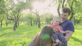 Het gelukkige jonge oudersaandeel kust in openlucht hun leuke babyjongen in park Langzame Motie stock footage