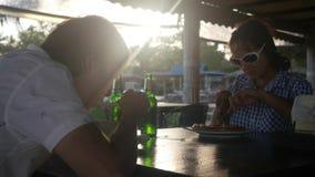 Het gelukkige jonge paar die maaltijd eten drinkt bier clinking flessen door de zon met de gevolgen van de lensgloed in koffie te stock videobeelden