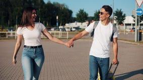 Het gelukkige jonge paar gaat met bagage dichtbij de luchthaven of het station Het concept reis, vakanties, vakantie stock videobeelden
