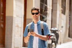 Het gelukkige jonge student mannelijke texting op zijn slimme telefoon in moderne stad royalty-vrije stock fotografie
