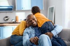 Het gelukkige jonge vader plakken op zijn zonen op bank stock foto's