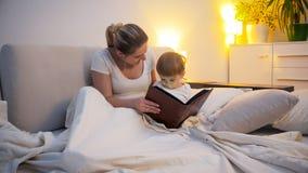 Het gelukkige jonge verhaal van de vrouwenlezing aan haar peuterzoon in bed bij nacht royalty-vrije stock fotografie
