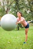 Het gelukkige jonge vrouw in evenwicht brengen op één been en het houden van geschiktheidsbal voor haar borst royalty-vrije stock fotografie