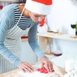Het gelukkige jonge vrouw gelukkig glimlachen hebbend pret met Kerstmisvoorbereidingen die Kerstmanhoed dragen Stock Foto