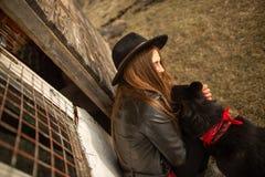 Het gelukkige jonge vrouw plaing met haar zwarte hond Brovko Vivchar in fron van oud blokhuis stock foto's