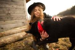 Het gelukkige jonge vrouw plaing met haar zwarte hond Brovko Vivchar in fron van oud blokhuis royalty-vrije stock foto's