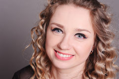 Het gelukkige jonge vrouw stellen over grijs Royalty-vrije Stock Foto's