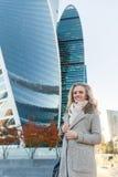 Het gelukkige jonge vrouw stellen tegen de achtergrond van moderne wolkenkrabbers Royalty-vrije Stock Foto's
