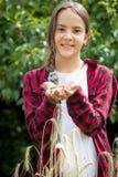 Het gelukkige jonge vrouwelijke landbouwer stellen op tarwegebied bij zonnige dag Stock Afbeeldingen