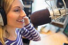 Het gelukkige jonge vrouwelijke radiogastheer uitzenden in studio Royalty-vrije Stock Foto's