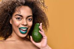 Het gelukkige jonge vrouwelijke stellen met tropisch fruit royalty-vrije stock afbeelding
