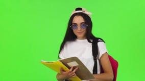 Het gelukkige jonge vrouwelijke student stellen met haar boeken en rugzak stock video