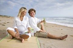 Het gelukkige jonge zwangere paar ontspannen op strand stock afbeeldingen