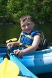 Het gelukkige jongen kayaking Royalty-vrije Stock Afbeeldingen