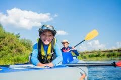 Het gelukkige jongen kayaking op de rivier op een zonnige dag tijdens de zomervakantie royalty-vrije stock foto's