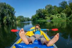 Het gelukkige jongen kayaking op de rivier op een zonnige dag tijdens de zomervakantie Royalty-vrije Stock Afbeeldingen