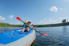 Het gelukkige jongen kayaking op de rivier op een zonnige dag tijdens de zomervakantie Stock Foto