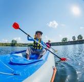 Het gelukkige jongen kayaking op de rivier op een zonnige dag tijdens de zomervakantie Stock Afbeelding