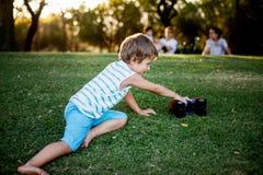 Het gelukkige jongen spelen met bal en stuk speelgoed auto op groen gras Royalty-vrije Stock Afbeelding