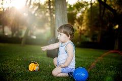 Het gelukkige jongen spelen met bal en stuk speelgoed auto op groen gras Stock Foto