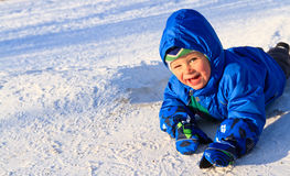 Het gelukkige jongen spelen in sneeuw Stock Fotografie