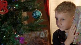 Het gelukkige jongen zoeken stelt onder de nieuwe jaarboom voor stock video