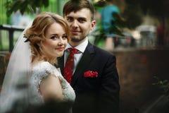 Het gelukkige jonggehuwdepaar die in openlucht in oude Italiaanse straat koesteren, is Stock Afbeelding