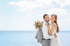 Het gelukkige jonggehuwdepaar koesteren Stock Foto