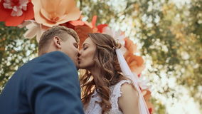 Het gelukkige jonggehuwdepaar kussen op de romantische huwelijksdoorgang met decoratie in de vorm van bloemen Het valt een straal stock videobeelden