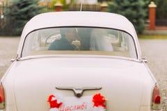 Het gelukkige jonggehuwdepaar kussen op een achterbank van retro auto, achtermening stock foto