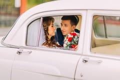 Het gelukkige jonggehuwdepaar zit op een achterbank van uitstekende auto Royalty-vrije Stock Foto