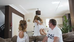 Het gelukkige Kaukasische paar zit op de laag het tijdje hun kinderen pret het spelen thuis in de woonkamer hebben stock footage