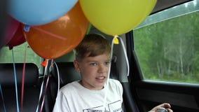 Het gelukkige kind berijden in een auto Feestelijke stemming, glimlach, gelach Ballons in de auto stock video