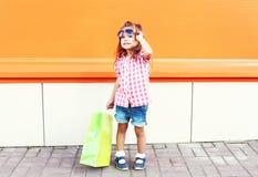 Het gelukkige kind dragen zonnebril met het winkelen zakken in stad over kleurrijke achtergrond Stock Afbeeldingen